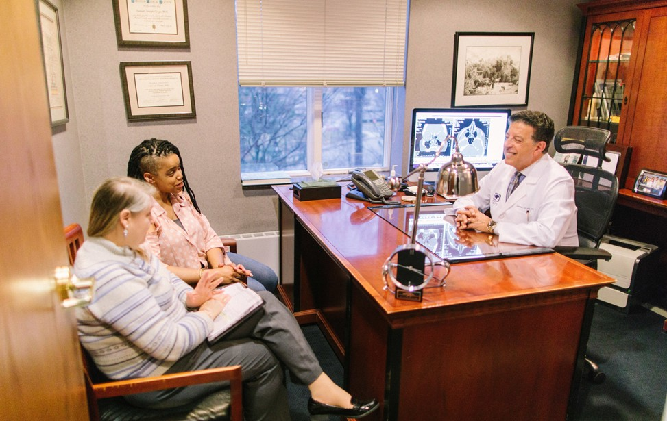Dr. Girgis consulting with patients in his office